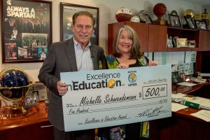 Michelle Schwendemann poses for a photo after accepting her Excellence in Education award from Michigan State University basketball coach Tom Izzo.