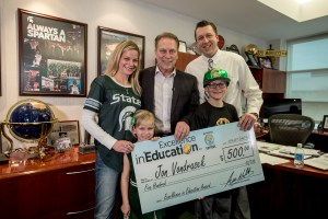 Jon Vondrasek poses for a photo with his wife, Kelly, daughter, Lily, and son Jaden, after accepting his Excellence in Education award from Michigan State University basketball coach Tom Izzo.