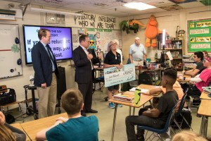 Tom Izzo talks with students in Linda Holzwarth's classroom while Lottery Commissioner, Aric Nesbitt (left), looks on.