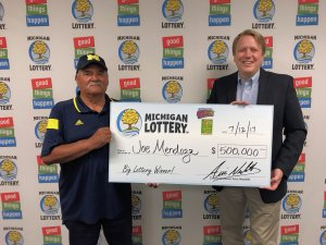 Joe Mendoza poses for a photo with Lottery Commissioner, Aric Nesbitt, after collecting his $500,000 prize.