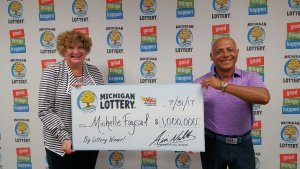 Michelle Faysal and her husband, Elie, pose for a photo after collecting her $1 million Mega Millions prize.