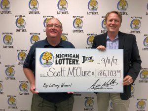 Scott McClure smiles while posing for a photo with Michigan Lottery Commissioner, Aric Nesbitt.