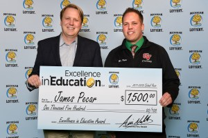 James Pecar poses for a photo with Michigan Lottery Commissioner, Aric Nesbitt, after accepting his Excellence in Education Award.