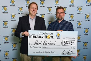 Mark Eberhard poses for a photo with Michigan Lottery Commissioner, Aric Nesbitt, after accepting her Excellence in Education Award.