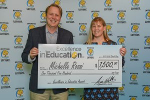 Michelle Rossi poses for a photo with Michigan Lottery Commissioner, Aric Nesbitt, after accepting her Excellence in Education Award.
