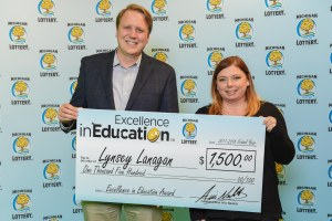 Lynsey Lanagan poses for a photo with Michigan Lottery Commissioner, Aric Nesbitt, after accepting her Excellence in Education Award.