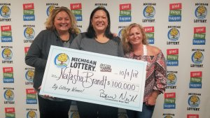 Natasha Brandt (center) smiles after collecting her $100,000 prize with friends Kelley White (left) and Brenna Lantz (right).
