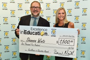 Shannon Wintz poses for a photo with Michigan Lottery public relations director, Jeff Holyfield, after accepting her Excellence in Education Award.