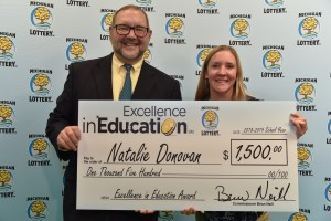 Natalie Donovan (right) poses for a photo with Michigan Lottery public relations director, Jeff Holyfield, after accepting her Excellence in Education Award.