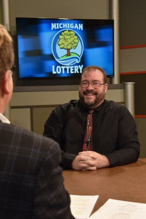 Aaron Smith is interviewed after being presented with an Excellence in Education award from the Michigan Lottery.