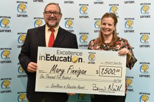 Mary Finnigan (right) poses for a photo with Michigan Lottery public relations director, Jeff Holyfield, after accepting her Excellence in Education Award.