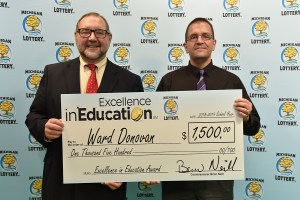 Ward Donovan (right) poses for a photo with Michigan Lottery public relations director, Jeff Holyfield, after accepting his Excellence in Education Award.