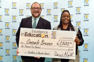 Consuelo Brewer (right) poses for a photo with Michigan Lottery public relations director, Jeff Holyfield, after accepting her Excellence in Education Award.