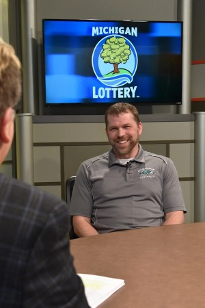 Kevin Bidwell is interviewed after being presented with an Excellence in Education award from the Michigan Lottery.