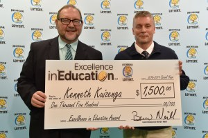 K. Mark Kuizenga (right) poses for a photo with Michigan Lottery public relations director, Jeff Holyfield, after accepting his Excellence in Education Award.