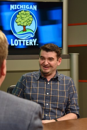 Jeremy Love is interviewed after being presented with an Excellence in Education award from the Michigan Lottery.