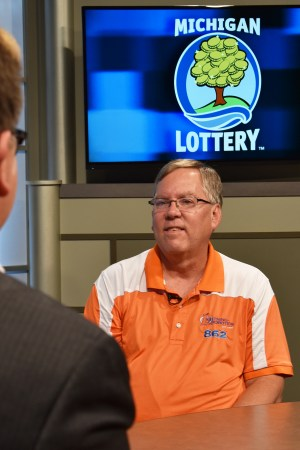 Jay Obsniuk is interviewed after being presented with an Excellence in Education award from the Michigan Lottery.