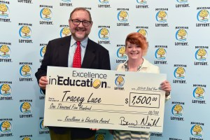 Tracey Luce (right) poses for a photo with Michigan Lottery public relations director, Jeff Holyfield, after accepting her Excellence in Education Award.