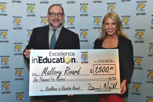 Mallory Rivard (right) poses for a photo with Michigan Lottery public relations director, Jeff Holyfield, after accepting her Excellence in Education Award.