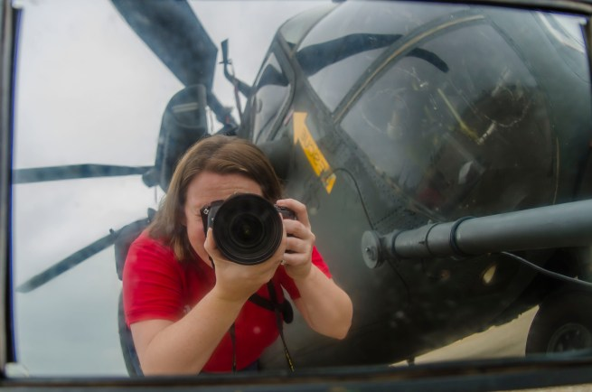Amanda with a camera reflected in the rearview mirror of a Blackhawk Helicopter.