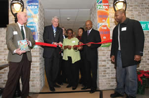 Gary White of PyraMax Bank (left) and Immanuel Mills of Focus on Energy (right) and other dignitaries watch as Mayor Tom Barrett, Lapham Park Resident Organization President Catherine Vance and Common Council President and Housing Authority Chair Willie L. Hines, Jr. cut a ribbon to celebrate the grand re-opening of Lapham Park.