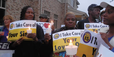 Home care workers and supporters light candles before ending the vigil with a prayer. (Photo by Maria Corpus)