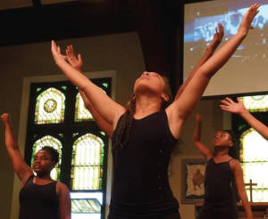 Taylor Burt (center) performs alongside her fellow dancers from the Sista to Sista dance company at All People's Church during the Black Lives Matter Art Showcase.