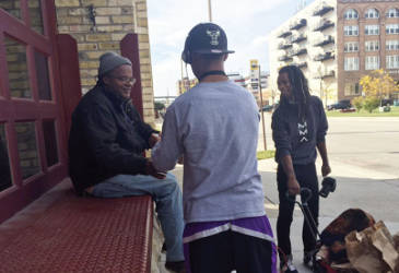 Lloyd Johnson and a volunteer offer a lunch bag to one homeless individual. Photo by Ariele Vaccaro.