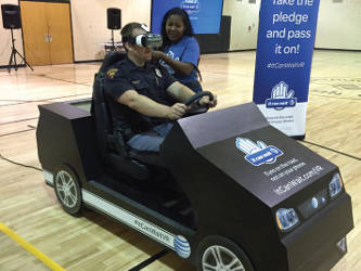 """State Trooper Michael Lawson takes a spin on the """"It Can Wait"""" texting and driving simulator. Photo by Dylan Deprey"""