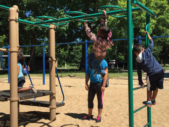 A four-year-old taking a try at the monkey bars. (Photo By Dylan Deprey)