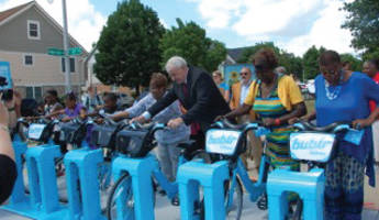 Mayor Tom Barrett tries out a Bublr bike with some Milwaukee Housing Authority residents at the ceremony that announced HACM's partnership with Bublr Bikes and Dreambikes. Photo By Bublr Bikes