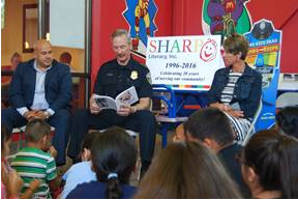 Alderman José Pérez (above left) and Lynda Kohler of SHARP Literacy joined Milwaukee Police Chief Ed Flynn as he read to 30 grade school students. The Books for Keeps program is sponsored by the Milwaukee Police Department and the 28 McDonald's restaurants within the city and features kid-sized library kiosks stocked with a variety of books for children to read and take home.