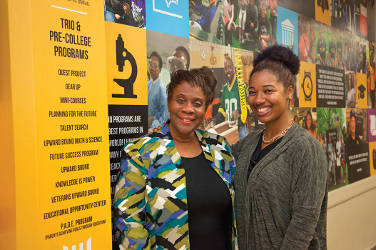 """April Holland (left) loves the mural outside her office at UWM's TRIO & Pre- College programs. """"Everyday I get to walk past our success stories,"""" said Holland, who directs the college-prep programs. Her newest colleague is Ka Shena Harris (right), who graduated from UWM in 2016 after several years in TRIO & Pre-College programs. (UWM Photo/Pete Amland)"""