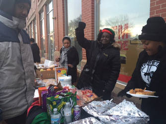 Lavita Booker of The Revolutionary Black Panthers offering hot food to people in need. (Photo by Karen Stokes)