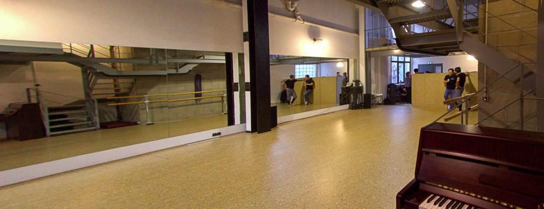 Salle de répétition, mirroirs, piano et barres de danse.