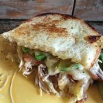 Elevated grilled cheese sandwich has pulled pork and California avocado with Cabot tomato basil cheddar.