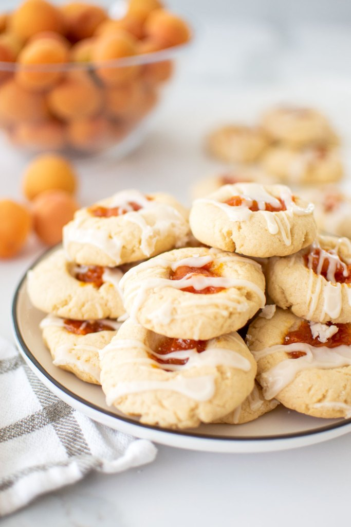 Easy Homemade Apricot Thumbprint Cookie recipe, the best thumbprint cookie recipe! Easy and delicious homemade Apricot Thumbprint Cookie Recipe. This easy thumbprint recipe uses fresh apricot jam, but you can also use any kind of jam you want. Easily make this thumbprint recipe gluten free with one simple adjustment. Buttery and sweet, thumbprints are filled with jam and mine are topped with a sweet glaze! Simple Apricot Thumbprint Cookie recipe. #organiccookies #cookierecipe #thumbprints #thumbprintcookies #apricotcookies #apricotjam #apricotthumbprints