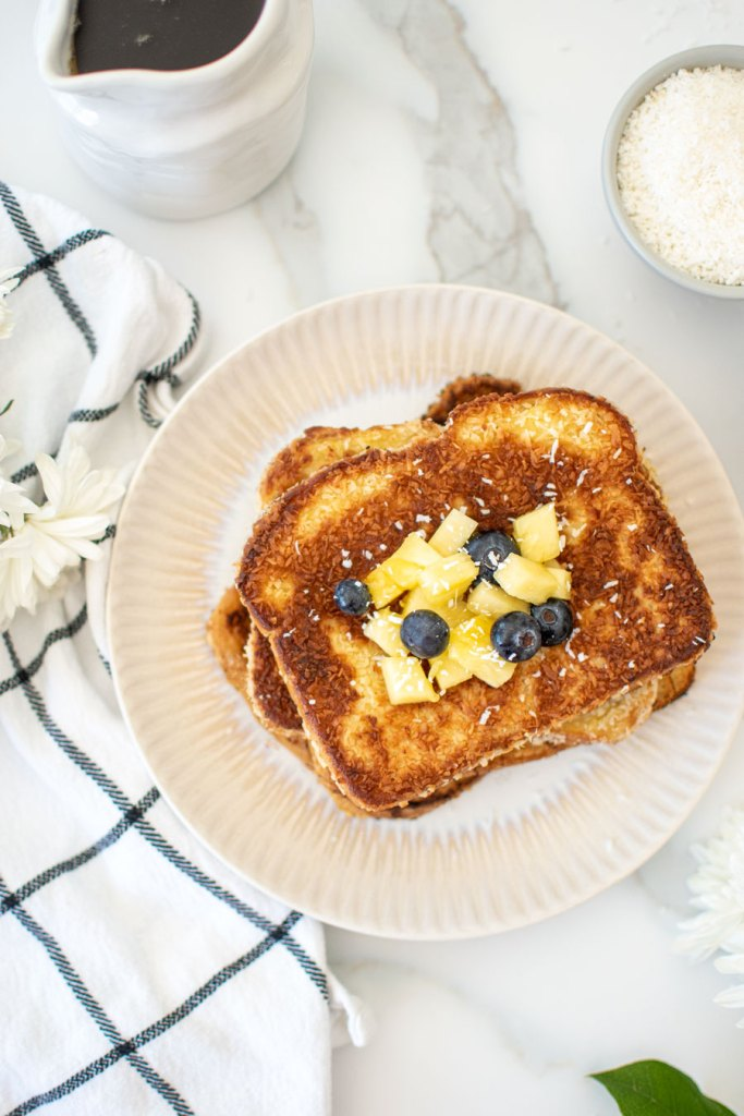 Light and delicious Coconut French Toast recipe that's so easy to make! This amazing French toast recipe is made with unsweeted organic coconut, coconut milk, and coconut oil for a lightened up version of French toast. Get this easy tropical Coconut French Toast recipe. #frenchtoast #organic #organicfrenchtoast #coconut #coconutfrenchtoast #organiccoconut #breakfastrecipe #brunchrecipe #brunchrecipes