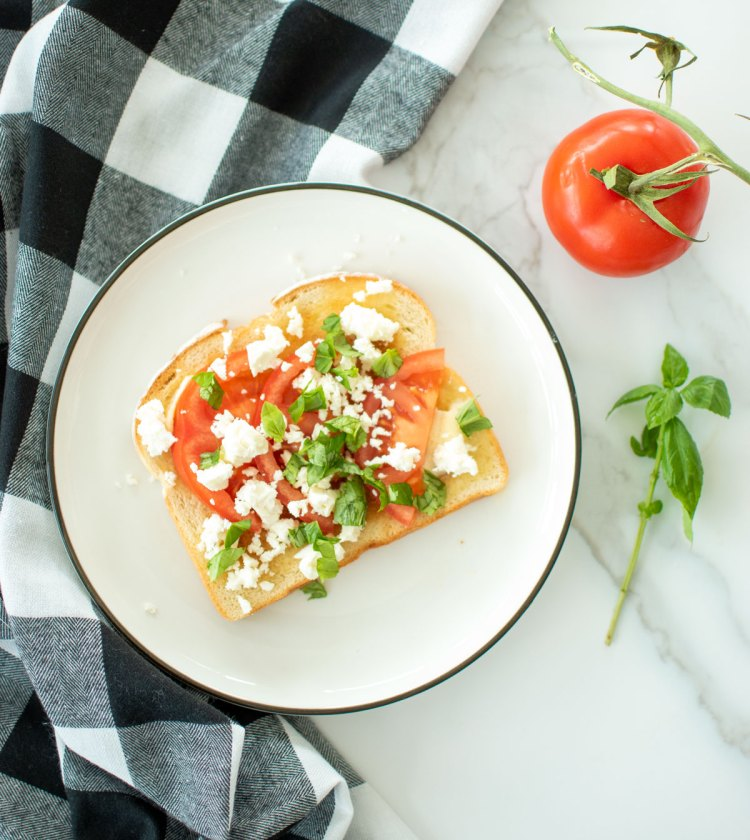 Easy and healthy Honey Butter Tomato Feta Toast recipe, the best breakfast or brunch recipe. This healthy toast is full of fresh tomatoes and basil along with feta for some protein. Make this easy toast recipe for breakfast, brunch or lunch! #toast #organictoast #healthytoast #toastrecipe #feta #fetatoast #honeybutter #honeybuttertoast