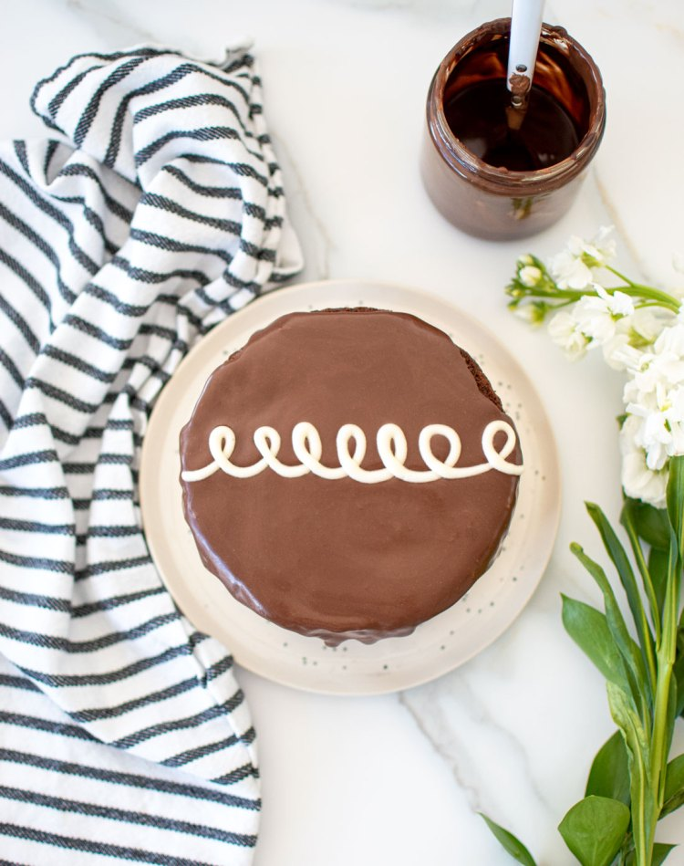Iconic Hostess Cupcake Cake recipe that's so good, better than the cupcakes! This easy chocolate cake is filled with delicious whipped cream filling, topping with dark chocolate ganache and the iconic squiggle decoration that it looks just like a giant Hostess Cupcake, but it's a Hostess Cake. #organiccake #hostesscupcake #hostesscake #hostess #whippedcreamfrosting #chocolatecake #chocolateganache #darkchocolate