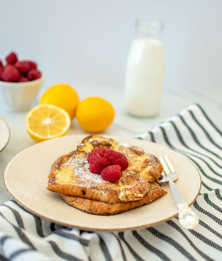 Easy and delicious Meyer Lemon French Toast recipe. This lighter recipe for French toast is one you'll love! This easy and fancy French toast recipe using fresh Meyer lemons and fresh raspberries. This is the perfect French toast recipe for a winter brunch or Valentine's Day #meyerlemon #frenchtoast #breakfastrecipe #brunch #brunchrecipe #lemonraspberry #organicbreakfast #organicrecipe #organicbrunch