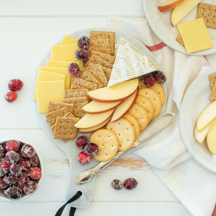 Easy and simple holiday cheeseboard recipe. This delicious cheeseboard is perfect for two. Easily add refill this DIY cheeseboard for larger parties. This Christmas cheeseboard would be delicious for any holiday #cheeseboard #organic #organiccheese #organiccrackers #holidayappetizer #appetizer #holidaycheeseboard