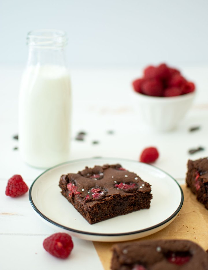 Easy sweet and salty Olive Oil Raspberry Brownie recipe that's perfect for Valentine's Day. This easy dark chocolate brownie recipe is filled with fresh raspberries and topped with course sea salt for a sweet and salty decadent dessert #organicbrownies #organicbaking #raspberries #raspberrybrownies #oliveoil #oliveoilbrownies #highaltitudebaking