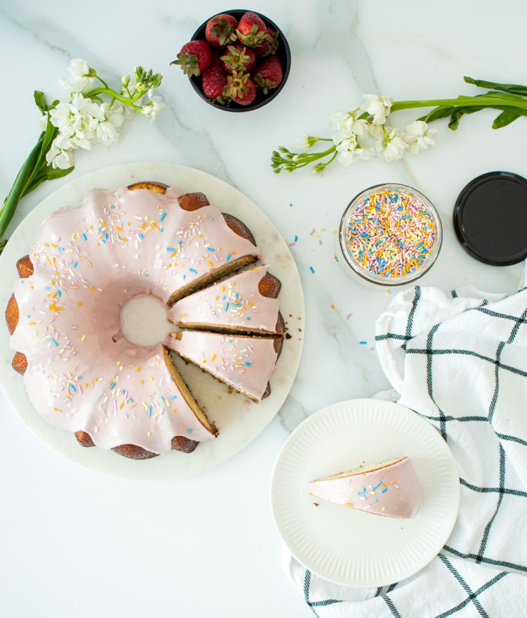 Easy Strawberry Donut Pound Cake recipe that's naturally colored. This simple and delicious pound cake only uses a few simple ingredients. Naturally colored in pastel pink, this strawberry donut look alike cake is perfect for breakfast, brunch, or dessert! #donut #pinkdonut #pinkdonutcake #strawberrydonut #pinkdonut #poundcake #highaltitudebaking
