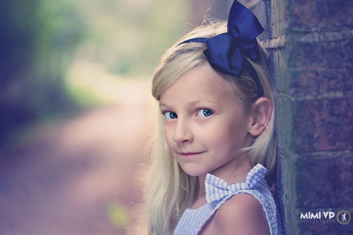 Little girl in blue summer dress looking at the camera