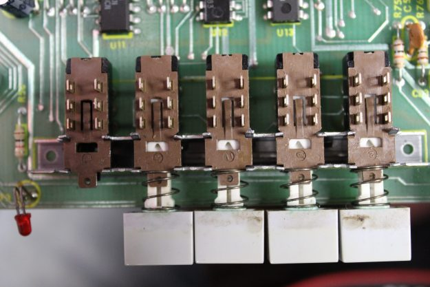 Figure 2: Programmable preset switches. The switch to far left has its' actuator removed. This is done by applying a precision flat-head screwdriver to the plastic lip between the lug sets.