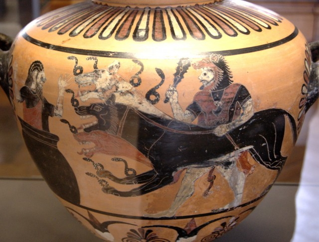 Heracles, wearing his characteristic lion-skin, club in right hand, leash in left, presenting a three-headed Cerberus, snakes coiling from his snouts, necks and front paws, to a frightened Eurystheus hiding in a giant pot. Caeretan hydria (c. 530 BC) from Caere (Louvre E701).