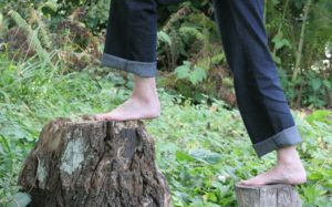 Iemand loopt met blote voeten over houten palen omhoog om contact te maken.