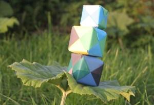 Een stapel van 3 gevouwen kubussen die vanuit werkelijke kracht balanceren op een blad.