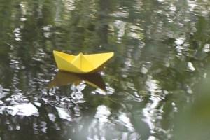 gevouwen bootje van geel papier dat vol passie vooruit drijft op rustig water